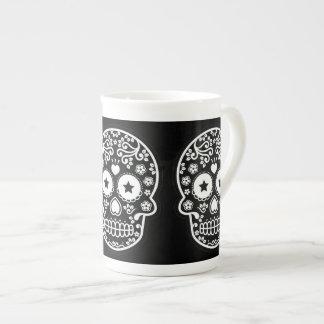 Ojos estrellados del cráneo blanco y negro del taza de porcelana