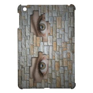 Ojos que miran a través de la pared de ladrillo