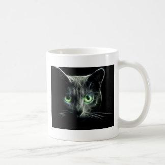 Ojos verdes que brillan intensamente del gato del taza de café