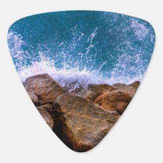 Ola oceánica que se estrella en rocas plumilla de guitarra