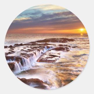 Olas oceánicas hermosas de la playa de la puesta etiquetas redondas