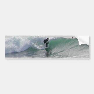 Olas oceánicas que practican surf a personas que p etiqueta de parachoque