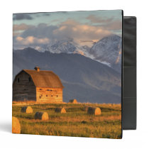 Old barn framed by hay bales and dramatic 3 ring binder