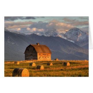 Old barn framed by hay bales and dramatic greeting card