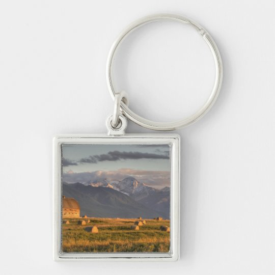 Old barn framed by hay bales and dramatic keychain