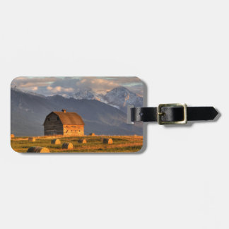 Old barn framed by hay bales and dramatic travel bag tag