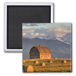 Old barn framed by hay bales and dramatic magnet