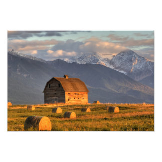 Old barn framed by hay bales and dramatic photo