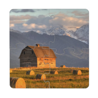 Old barn framed by hay bales and dramatic puzzle coaster