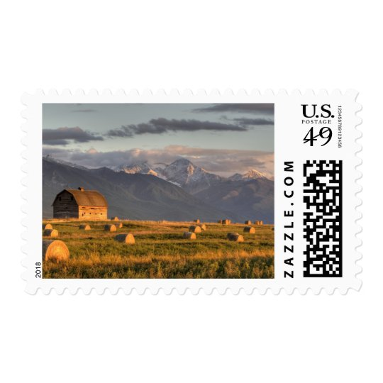 Old barn framed by hay bales and dramatic postage