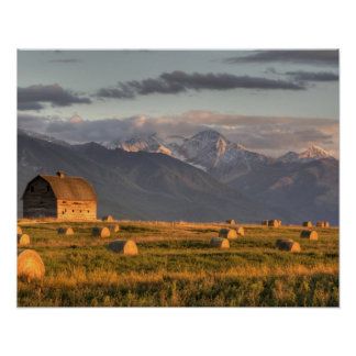 Old barn framed by hay bales and dramatic poster