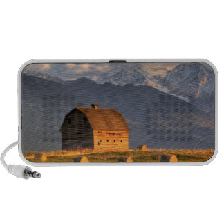 Old barn framed by hay bales and dramatic laptop speaker