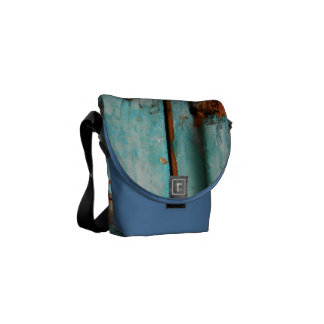 Old blue wooden door with rusted latch courier bag