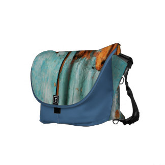 Old blue wooden door with rusted latch messenger bag