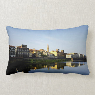 Old buildings line a river throw pillows