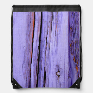Old cracked purple paint on wood drawstring backpack