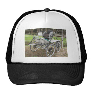 Old-fashioned horse carriage on green background trucker hat