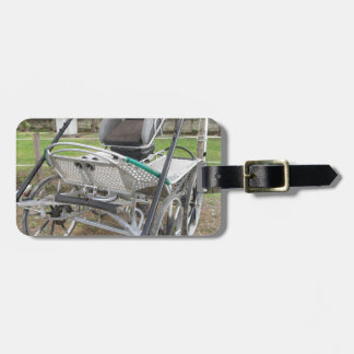 Old-fashioned horse carriage on green grass luggage tag