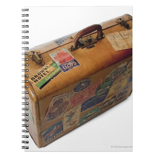 old fashioned suitcase with travel stickers spiral notebook