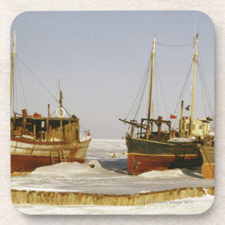 Old-fashioned, weathered fishing boats beached coaster