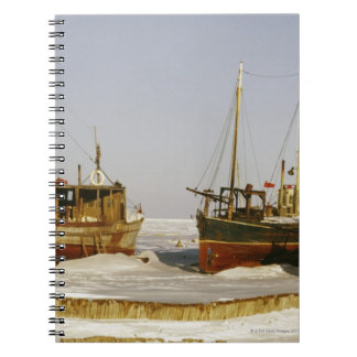Old-fashioned, weathered fishing boats beached notebook