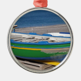 Old green fishing boat on beach. metal ornament