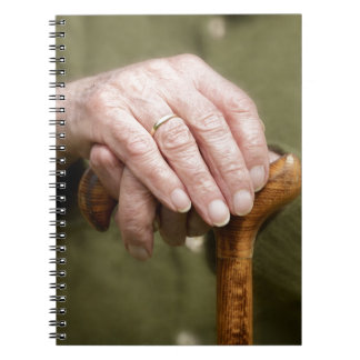 old hands OF A senior lean on walking stick Notebook