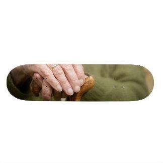 old hands of a senior lean on walking stick skateboard