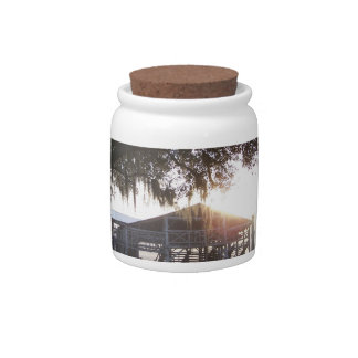 Old ranch building under trees with man statue candy jar