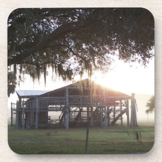 Old ranch building under trees with man statue beverage coasters