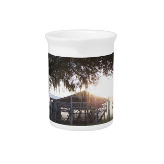 Old ranch building under trees with man statue drink pitcher