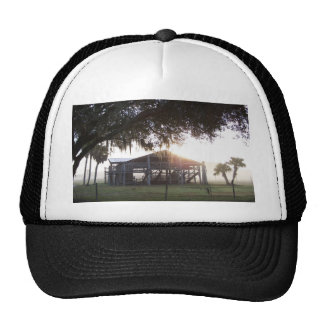 Old ranch building under trees with man statue trucker hat