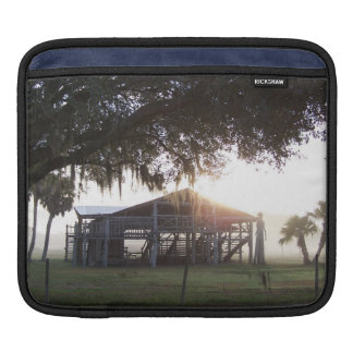 Old ranch building under trees with man statue iPad sleeves
