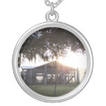 Old ranch building under trees with man statue necklace