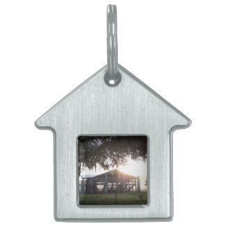 Old ranch building under trees with man statue pet tag