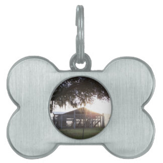 Old ranch building under trees with man statue pet name tags