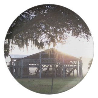Old ranch building under trees with man statue dinner plates