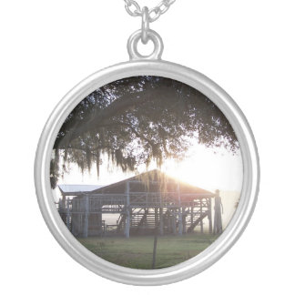 Old ranch building under trees with man statue round pendant necklace