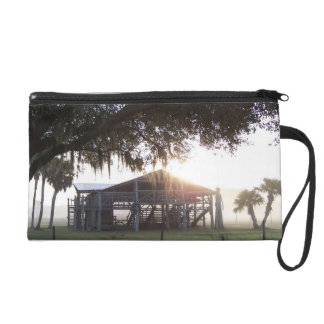 Old ranch building under trees with man statue wristlet purse