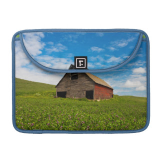 Old, red barn in field of chickpeas sleeves for MacBook pro
