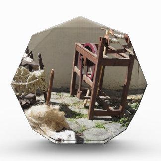 Old spinning wheel, raw wool yarn and wool to card acrylic award