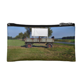 Old Tractor Trailer on a Green Field Cosmetics Bags