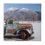 Old truck sitting in the field small square tile