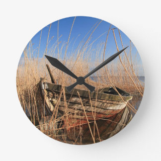 Old wooden boat in the reeds wallclock
