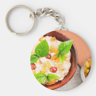 Old wooden bowl of healthy oatmeal with berries keychain