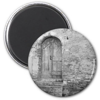 Old wooden door in old brick wall. Black and white Magnet