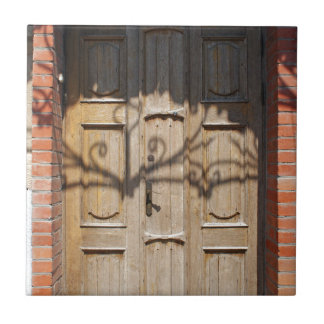 Old wooden door of unpainted wood with curly strip ceramic tile