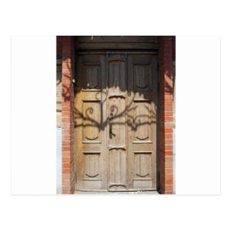Old wooden door of unpainted wood with curly strip postcard