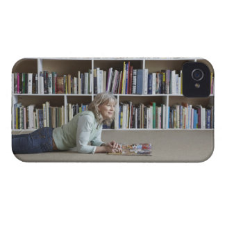 Older woman reading by bookshelves iPhone 4 cover
