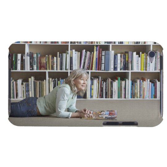 Older woman reading by bookshelves iPod Case-Mate case